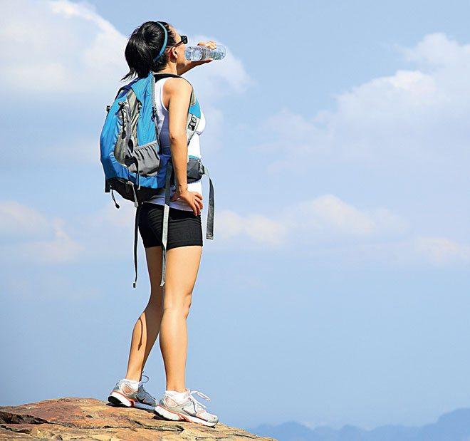 corredora bebendo água em corrida de montanha