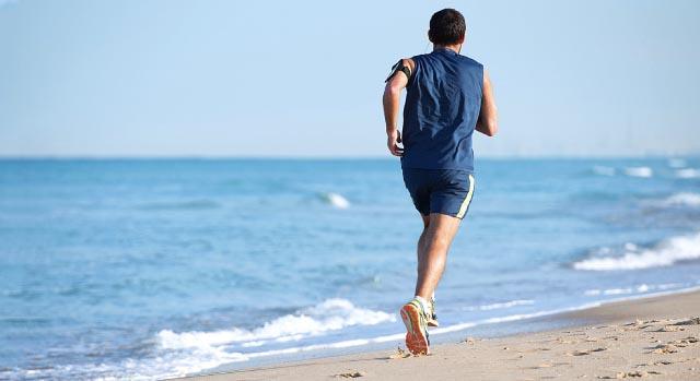 Homem correndo na areia