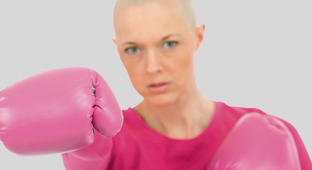 Mulher com câncer lutando com luvas de boxe