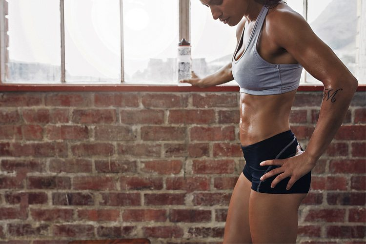 Mulher na academia com abdomen trancado