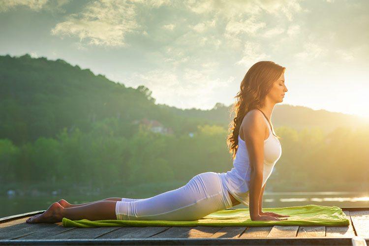 Mulher praticando ioga no campo